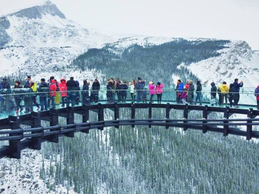 A multitude of brightly dressed tourists line the glass-bottomed Skywalk