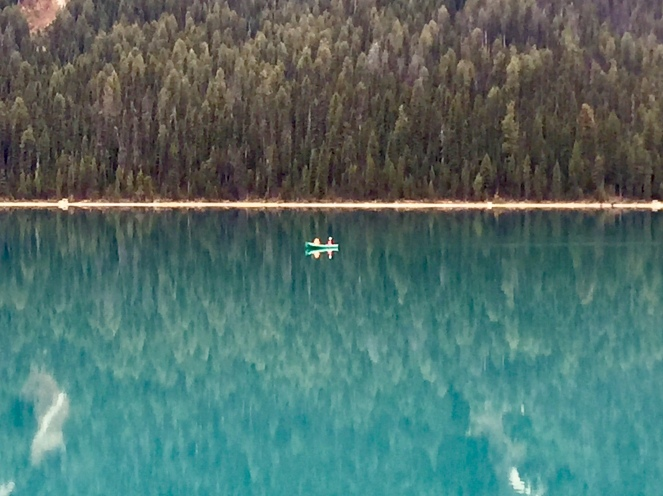 A single kayak disturbs the still turquoise waters of Emerald Lake