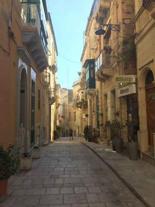 Narrow street with male pedestrian. Birgu Street. Three Cities, Malta